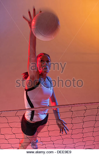 Volleyball player spiking ball over net - Stock Image