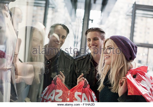 Young couple window shopping with sale shopping bags,  New York, USA - Stock Image