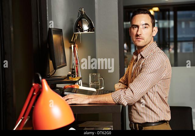 Portrait of businessman at office desk - Stock Image