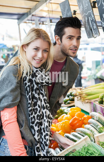 Young couple at greengrocer's shopping for fresh fruits and vegetables - Stock Image