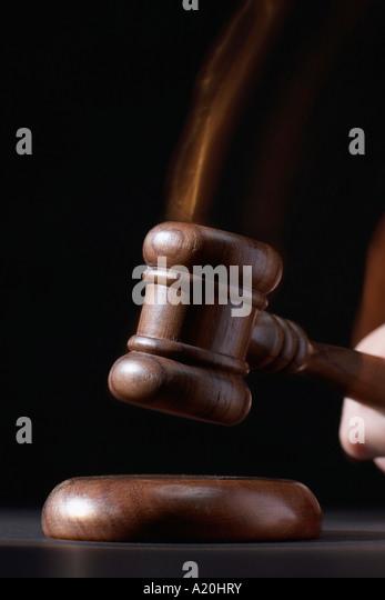 Gavel hitting base, black background - Stock Image