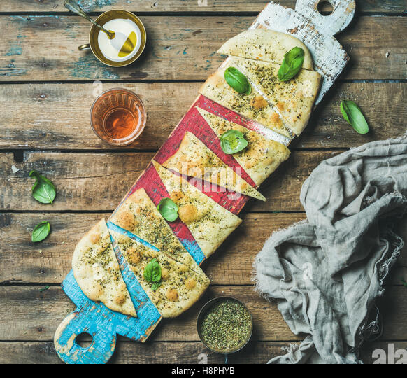 Focaccia with basil leaves, olive oil, wine on colorful board - Stock Image