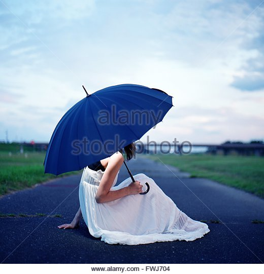 Side View Of Woman With Umbrella Sitting On Road - Stock Image