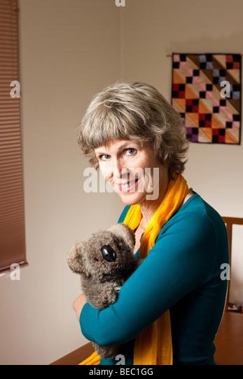Mature lady with a stuffed Koala bear toy - Stock Image