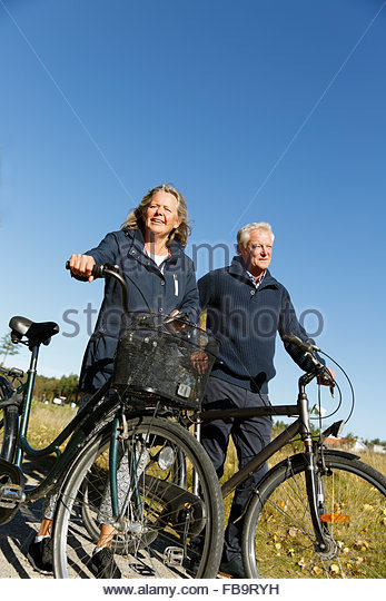 Sweden, Sodermanland, Senior man and mature woman walking with bicycles - Stock-Bilder
