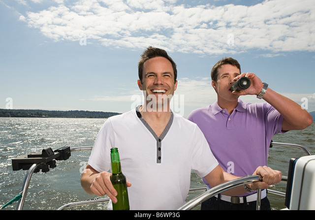 Male friends sailing a boat - Stock Image