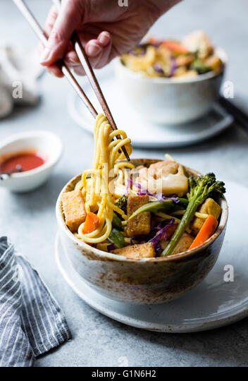 Curried noodles with crispy tofu & winter vegetables, gluten-free and vegan. - Stock Image