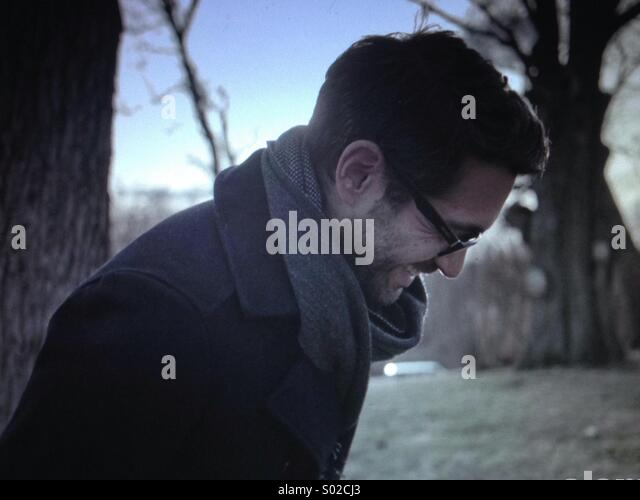 A dark haired man laughs at winter - Stock Image