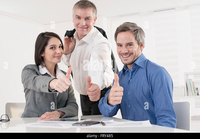 business team at office showing thumb up - Stock Image