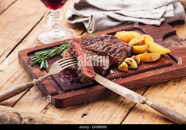 Medium rare grilled Beef steak Ribeye with roasted potato wedges on cutting board on dark wooden background - Stock Image