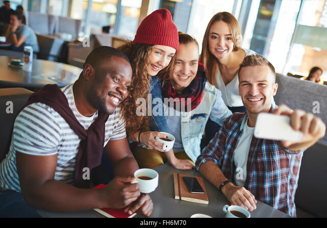 Modern teenage friends making selfie while gathering in cafe - Stock Image