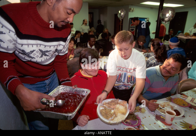 New Jersey Passaic Salvation Army Thanksgiving meal volunteers serve homeless poor Black man boy woman free food - Stock Image