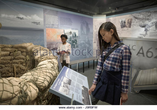 Curious girl student looking at exhibit on field trip in war museum - Stock-Bilder