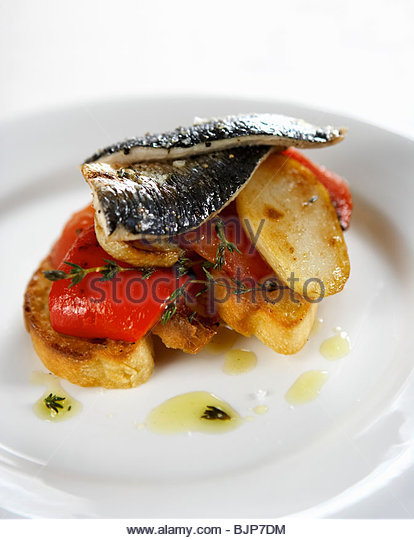 Fried sardines on potatoes and peppers - Stock Image