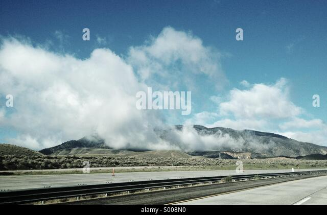 High up in the hills, a storm has passed and clouds drift over the open road. - Stock Image
