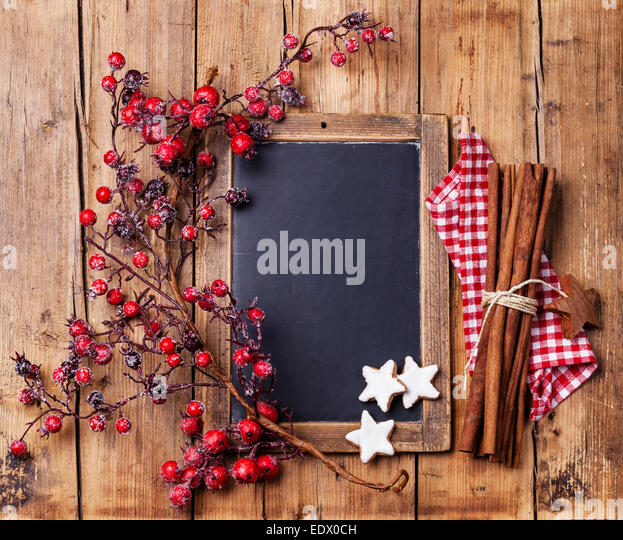 Vintage Christmas background with chalk board, branch with red berries, Xmas cookies and cinnamon sticks - Stock Image