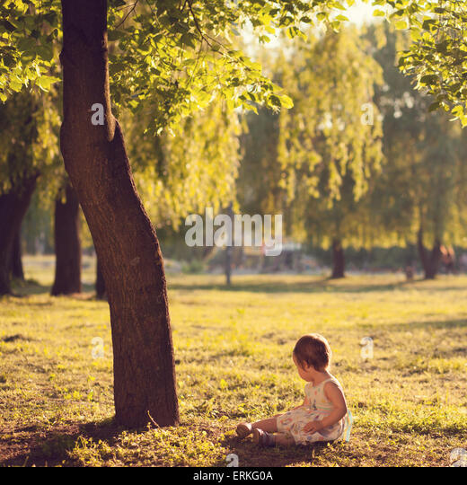 toddler sitting under the tree - Stock Image