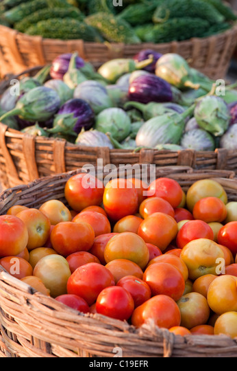 Aubergines / Eggplant , Tomatoes and Bitter gourd in baskets at an Indian market - Stock Image