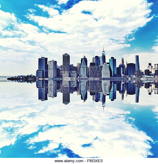 City Skyline By Calm Lake Against Cloudy Sky - Stock Image