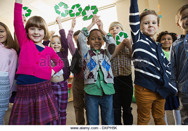 Portrait of children holding recycling symbols in school - Stock Image