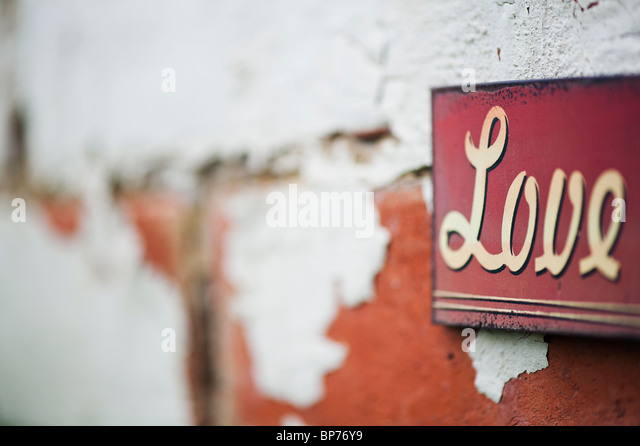 Love. Old metal garden sign on a painted brick wall - Stock Image
