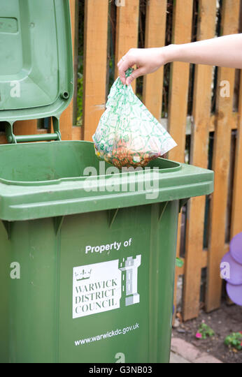 Kitchen food waste being placed into a green garden waste bin for recycling. - Stock Image