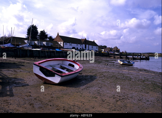 BURNHAM OVER SAITHE NORFOLK England UK March Lone red and white rowing boat beached at low tide the village is in - Stock Image