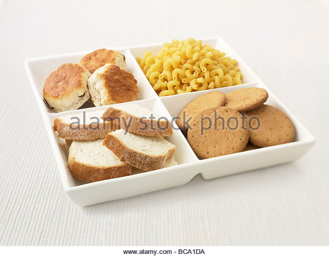 Close up of sectioned plate with pasta, cookies, bread and biscuits - Stock Image