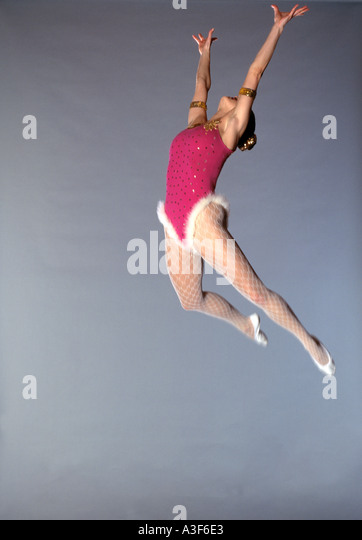 trapeze artist flying through the air grey background - Stock Image
