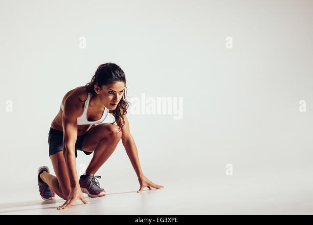 Female athlete in position ready to run over grey background. Determined young woman ready for a sprint. - Stock Image