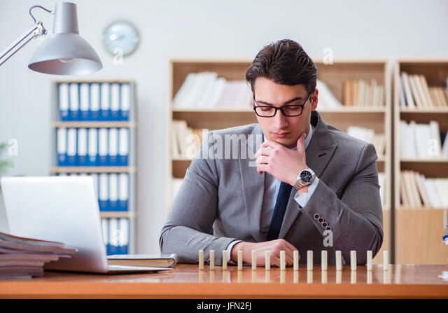 Businessman with dominoes in the office - Stock Image