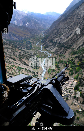 An aerial gunner surveys the surrounding area during a combat mission in Afghanistan. - Stock Image