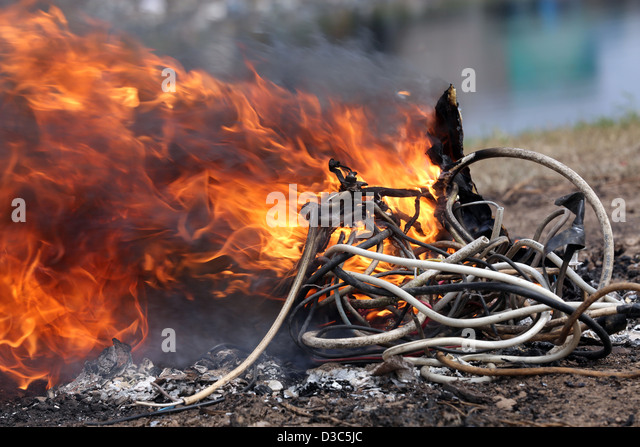Burning cables from computers and other electronics to recover copper near the Agbogbloshie slum in Accra, Ghana - Stock Image