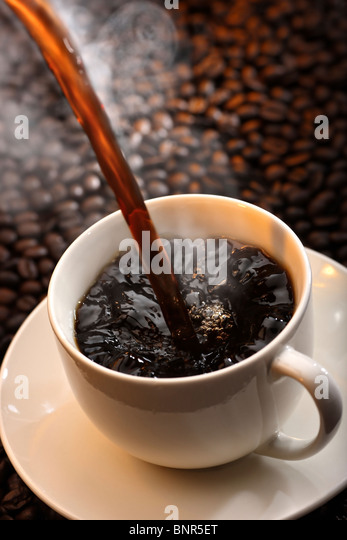 Pouring a cup of traditional steaming hot coffee against coffee-bean background - Stock-Bilder