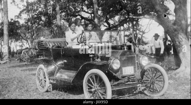 Full length portrait of three African American girls driving a car outdoors on grass under a tree, one man watching - Stock Image