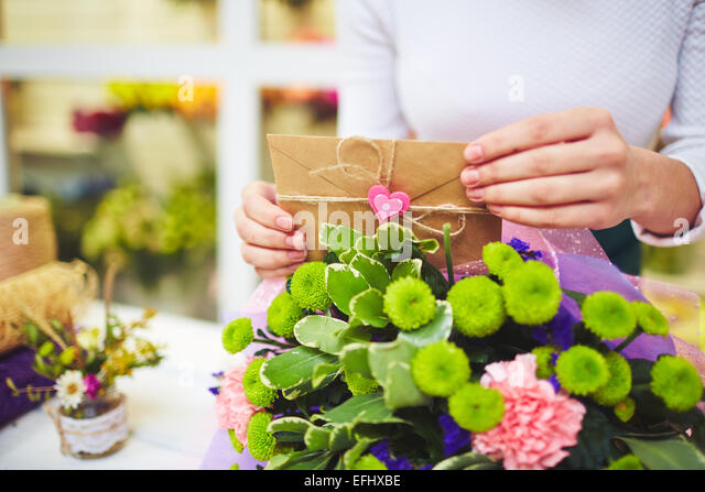 Female hands with love message putting it in floral bouquet - Stock-Bilder