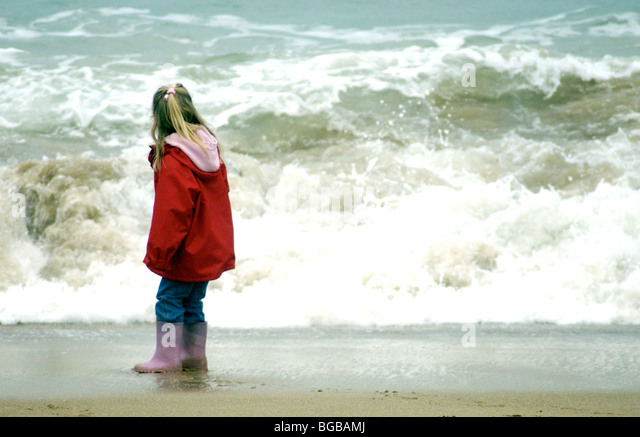 Young girl looking at a big wave on the beach in the winter. - Stock-Bilder