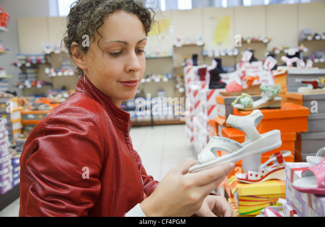 mother in a supermarket chooses children's footwear, white summer barefoot persons - Stock Image