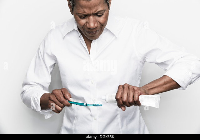Senior woman struggling to squeeze toothpaste onto toothbrush - Stock-Bilder