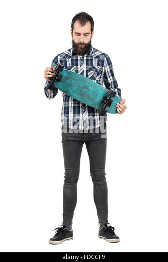 Young hipster in tartan shirt holding skateboard looking down. Full body length portrait isolated over white studio - Stock Image