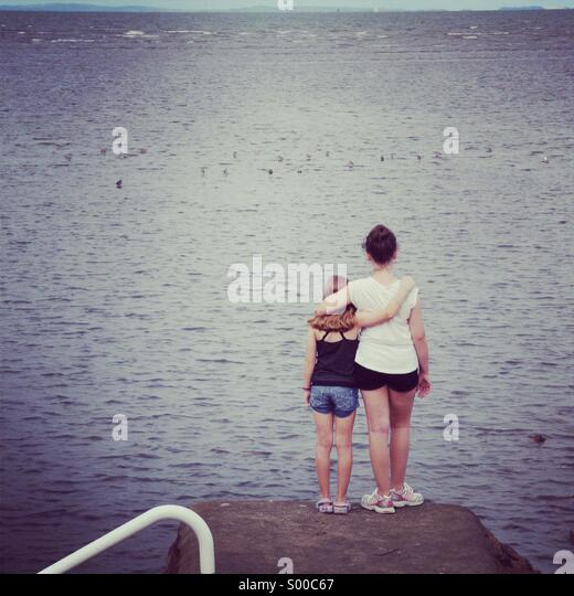 Two young girls hug at the seaside. - Stock Image