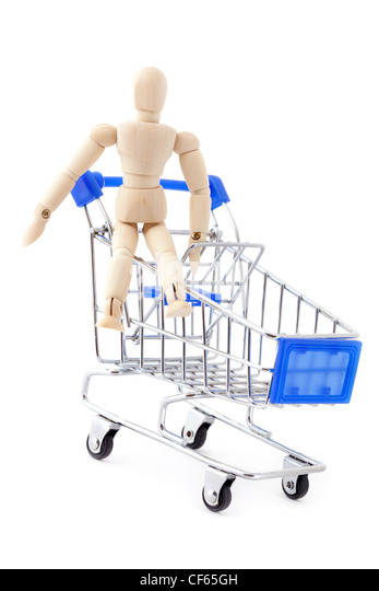 Shopping concept. Wooden doll sitting in the metal shopping cart. - Stock Image