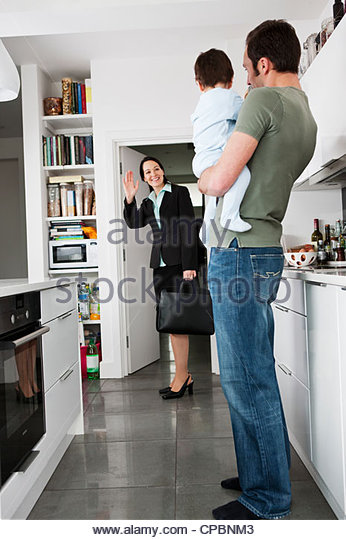 A mother leaving for work, waving goodbye to her partner and baby son - Stock Image