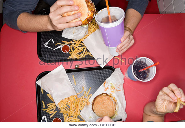 Overhead view of couple eating fast food - Stock-Bilder