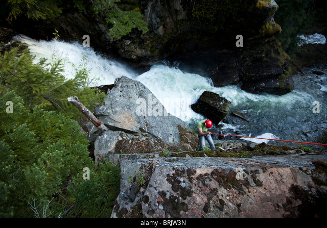 A young man rappels down a cliff next to a waterfall in Idaho. - Stock Image