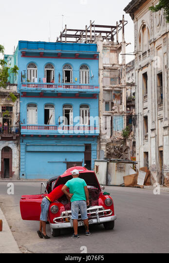 Two cuban men fixing their car in the middle of the street in Old Havana, Cuba. - Stock-Bilder