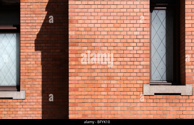 Red brick wall with windows - Stock Image