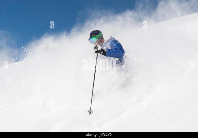 Skier going through fresh powder in the ski region of Disenits,Switzerland - Stock Image