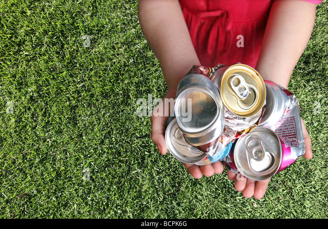 Aluminum Cans Crushed For Recycling in a Childs Hands - Stock Image
