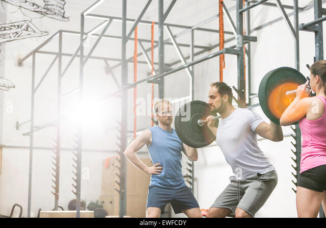 People assisting man in lifting barbell at crossfit gym - Stock Image